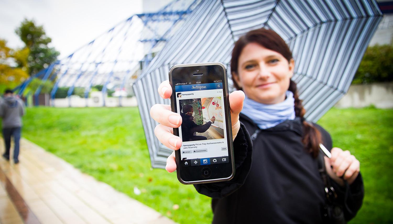Une joueuse montre son téléphone, avec lequel elle prolonge son expérience de jeu