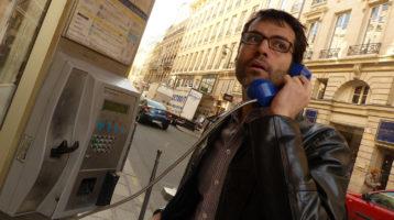 un joueur écoute un indice dans une cabine téléphonique